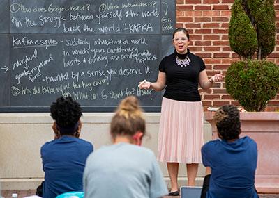 Female professor standing in front of a blackboard teaching a class outside