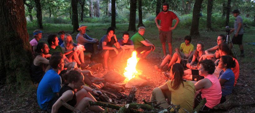 Dr. Kip Redick with a group of students around a campfire