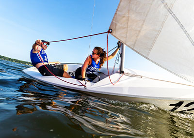 Two members of the sailing team adjust the sail on boat number 12