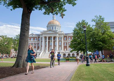 Students walking with Christopher Newport Hall behind