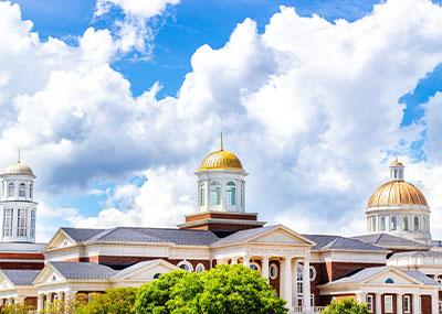 Three CNU cupolas against a blue sky with clouds