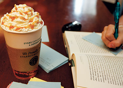 Caramel latte in front of an open book and study cards