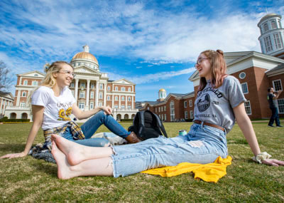 Two girls sitting on the great lawn and laughing