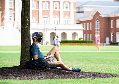 Male student sitting under a tree on the Great Lawn with a book