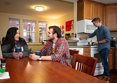 Students talking at a kitchen table while another student cooks in the background