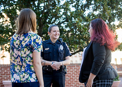 Campus police office talking with two students
