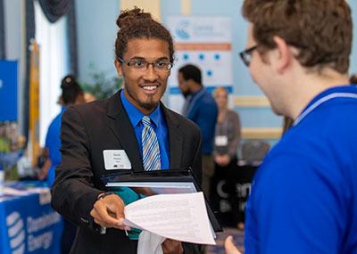 Student handing in resume at career fair