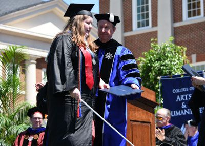 Blind student walking across the stage at Commencement