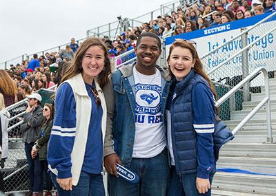 Three students smiling at homecoming game