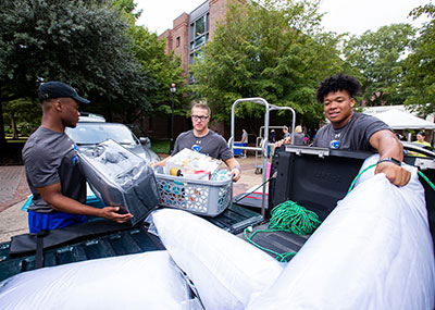 Three male students helping unload the bed of a truck during move in week
