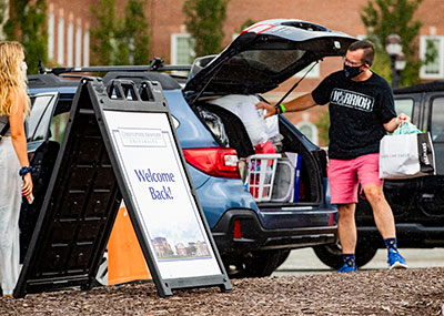 Parent helping his student unload the car to get ready for move in with a sign in front saying Welcome Back