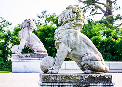 Side view of two lion statues at the entrance to the Lion's Head Bridge