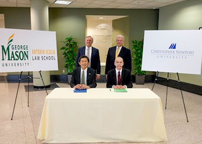 Leaders from CNU and GMU sign the agreement.