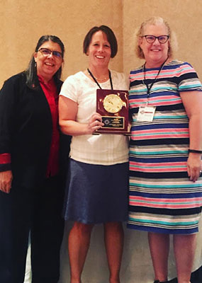 Dr. Lynn Shollen (center) accepts the Outstanding Program Award from the Association of Leadership Educators' Barbara Altman (left) and Gina Matkin.