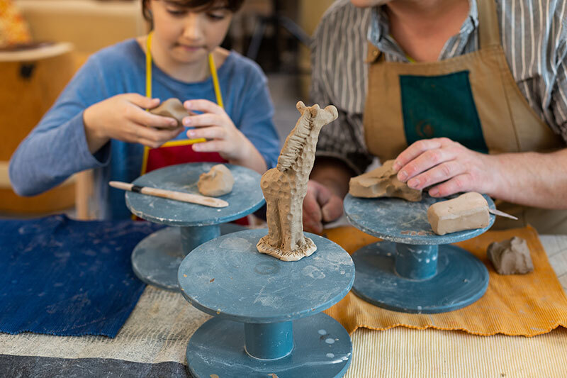 Child and teacher sculpting clay animals