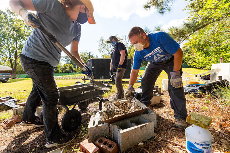 Dr. Russell Burke (right) and students build artificial reef components