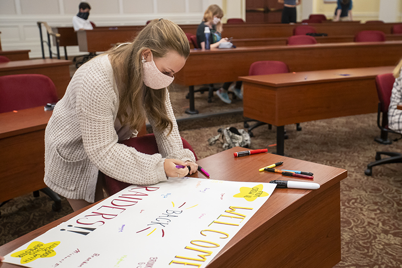 A student writes on a poster for Newport News Public Schools students
