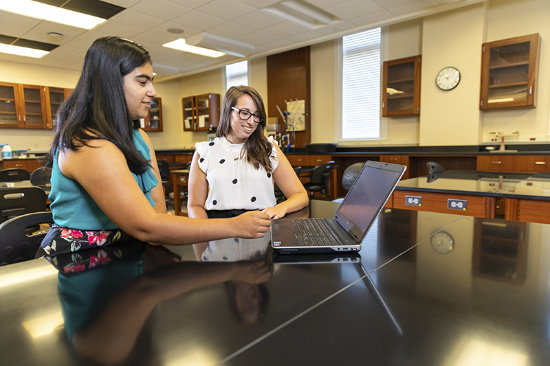 Psych Professor Dr. Leslie Rollins (right) works with a student (file photo)