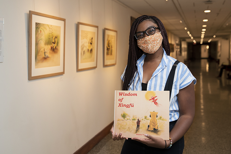 Whitney Truitt in the Ferguson Hall Gallery with her book, Wisdom of Xingfu