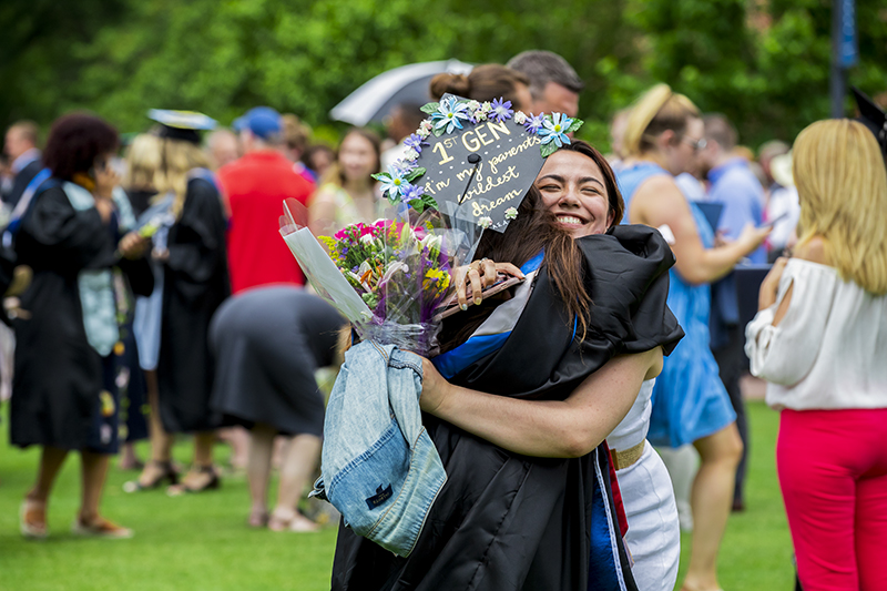 Graduates embrace on the Great Lawn