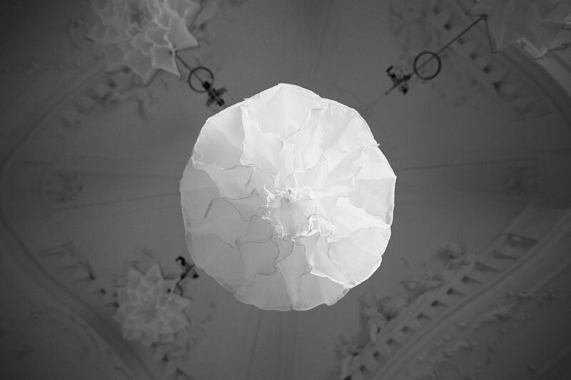 black and white image of looking up at a shylight installation silk light shade in the open position