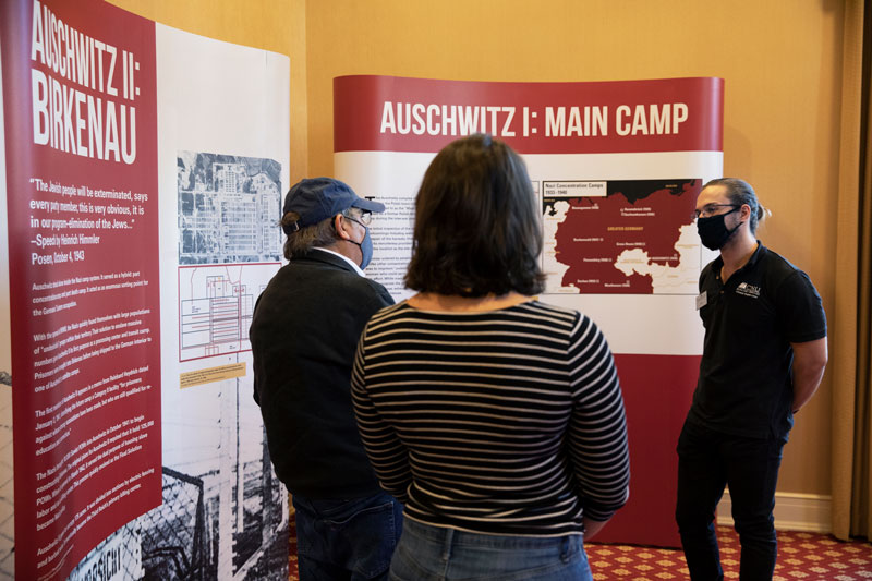 Dr. Richard Freund (left) speaking with Christopher Newport students in front of one of the Auschwitz photo exhibit panels