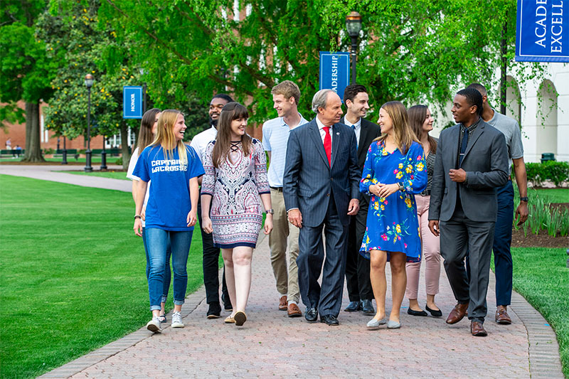 President Paul Trible (center) walks with students on the Great Lawn in 2019.