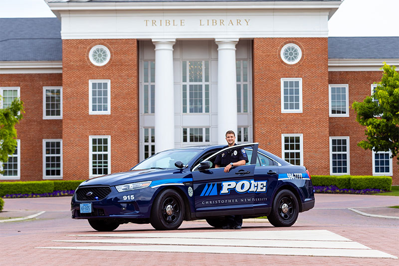 CNUPD Officer Caden Butler in front of Trible Library