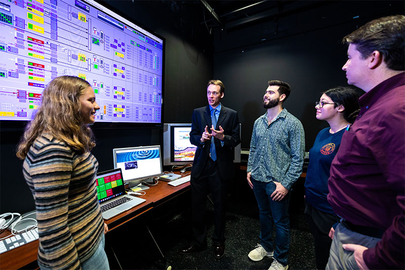 Dr. Ryan Fisher (center) speaks with students in the Advanced Laser Interferometer Gravitational-wave Observatory at CNU