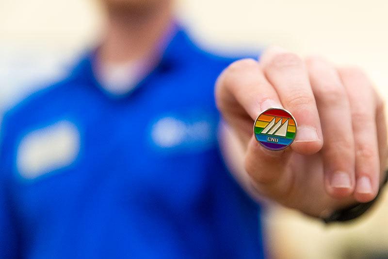 Staff member holding LGTBQ affinity group lapel pin