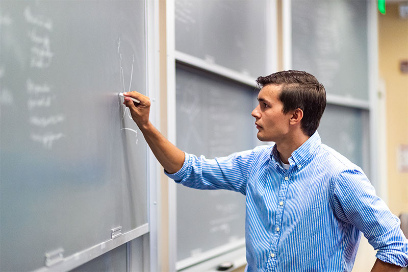 Michael Sparks working on a math problem on a chalkboard