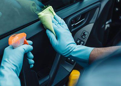 gloved hands cleaning interior car door panel