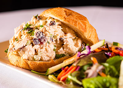 Chicken salad on a croissant with a side salad