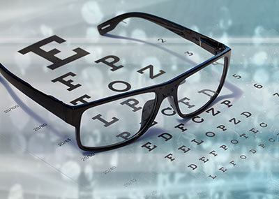 Glasses on top of an eye exam chart