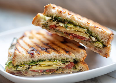 Basil, tomato and cheese panini sandwich on a white plate