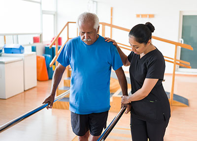 Physical therapist helping a patient walk