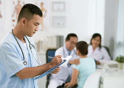 Physicians assistant taking notes while doctor talk with patient in the background
