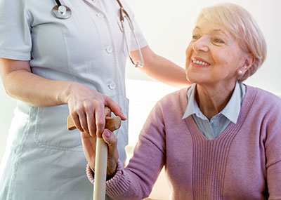 Doctor helping a senior lady stand up