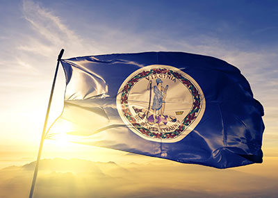 Virginia state flag against the sky at sunset